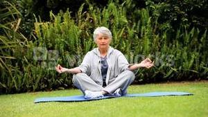 Greyhaired woman doing yoga in the garden