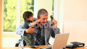 Man in suit minding baby and trying to do office work