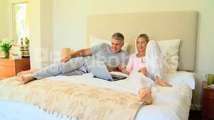 Attractive couple relaxing on bed with laptop