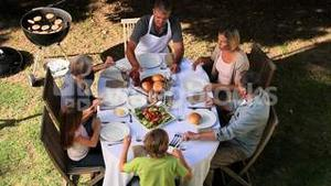 Family sorting out cutlery at the garden table before eating