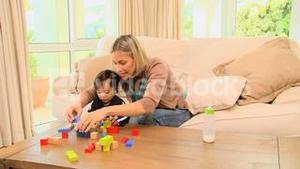 Young mother showing her baby how to fit blocks together
