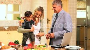 Baby holding bread and fidgeting while his parents are laughing