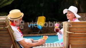 Mature couple drinking cocktails by swimming pool