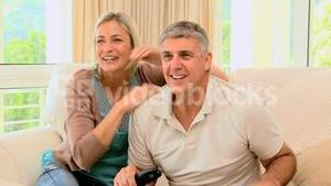 Couple excitedly watching sports on tv
