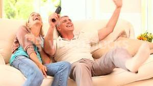 Very happy couple watching sports on tv