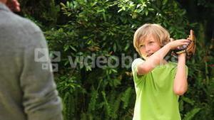 Boy playing with baseball with father in garden