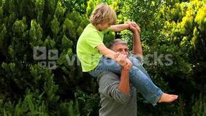 Man carrying his son on his shoulders in the garden