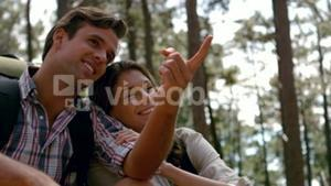 Smiling couple pointing away on a hike