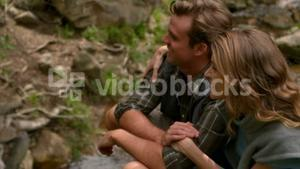 Happy hiker couple sitting near the river