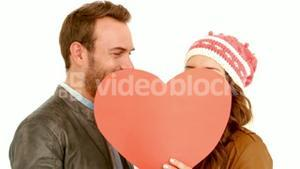 Young couple covering their face with a pillow heart