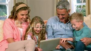 Smiling family using technology on sofa