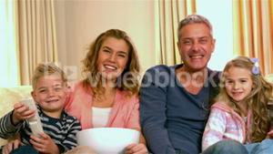 Smiling family watching tv eating popcorn