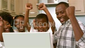 Happy black family rejoicing and using laptop