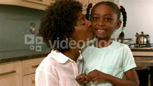 Smiling mother kissing daughter in kitchen