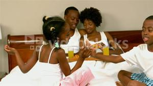 Happy family in bed with kids playing