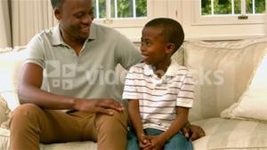 Father and son talking on sofa
