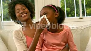 Mother helping daughter blowing her nose