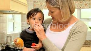 Mother giving food to her son