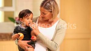 Mother giving food to her little son