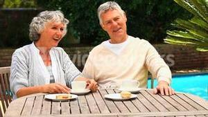 Mature couple having a snack by a swimming pool