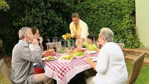 Family with grandparents eating outdoors