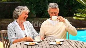 Mature couple laughing over coffee