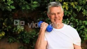 Mature man doing exercise with dumbbells