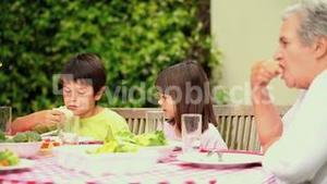 Children eating in the garden with their family