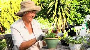 Mature woman potting plants in the garden