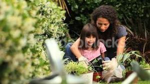 Little girl helping her mother with the gardening