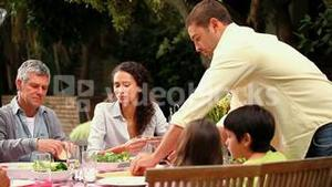 Family lunch with grandparents outdoors
