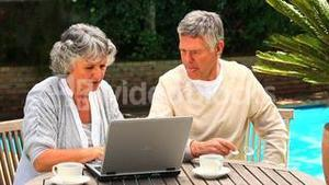 Mature couple sitting outdoors using a laptop