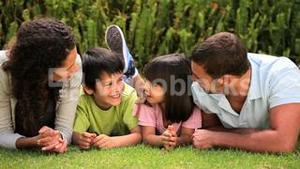 Family lying laughing on the lawn