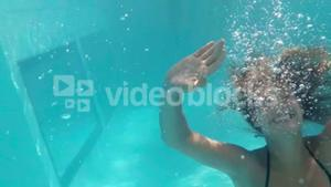 Pretty woman swimming underwater in pool