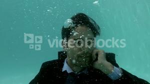 Businessman using smartphone underwater