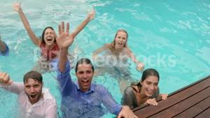 Happy friends with clothes in the pool