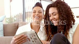 Happy lesbian couple reading magazine