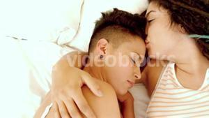 Happy lesbian couple on bed