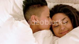 Happy lesbian couple on bed under blanket