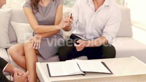 Smiling couple signing contract for new house