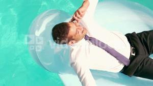 Businessman having a phone call on inflatable
