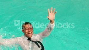 Dressed businessman in swimming pool