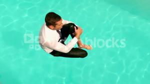 Businessman jumping in the swimming pool