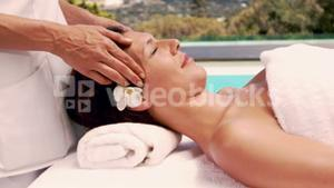 Relaxed woman getting a head massage poolside