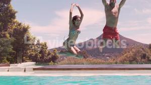 Happy couple jumping in the swimming pool