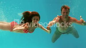 Couple with thumbs up swimming underwater