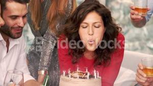 Smiling woman blowing the candles