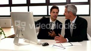 Businessmen talking and pointing computer monitor