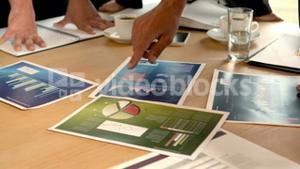 Graphics on table looked by business people in meeting