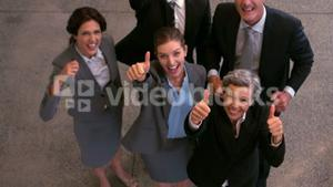 Happy business team showing thumbs up